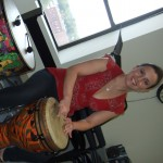 Stephanie gearing up for kiddie music time and rocking out on the Djembe